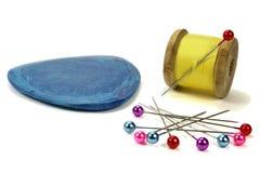 Bobina de madera con los hilos, la aguja, la tiza azul y pernos para coser en un fondo blanco Imagenes de archivo