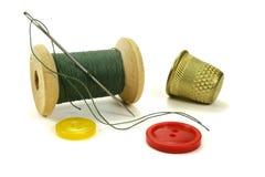 Bobina de madera con los hilos, la aguja, los botones del color y el dedal para coser en un fondo blanco Fotografía de archivo