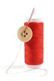 Bobina del filo rosso con l'ago e del bottone isolato su bianco Fotografie Stock Libere da Diritti