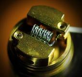 Bobina del nicromo, vape del cavo del nicromo su un oro del dispositivo di gocciolamento vaporizer immagine stock