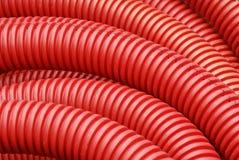 Bobina del tubo acanalado de la plomería del plástico rojo Fotos de archivo