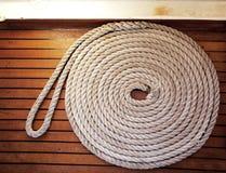 Bobina della corda attraverso il decking del teck Fotografie Stock Libere da Diritti