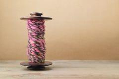 Bobina della ruota di filatura con il filato rosa e marrone della mano Fotografia Stock Libera da Diritti