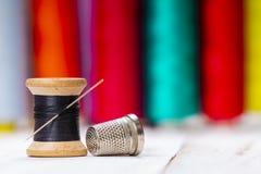 Bobina di cucito di legno con il ditale nero del metallo e del filo immagini stock libere da diritti