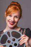Bobina di film attraente della tenuta della testarossa fotografie stock