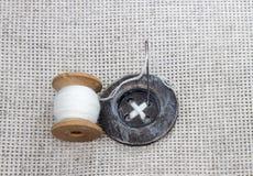 Bobina di legno con il filo bianco, ago e cucito Immagini Stock