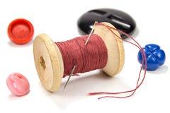 Bobina di legno d'annata del filo, dell'ago e dei bottoni rossi su fondo bianco Fotografia Stock Libera da Diritti
