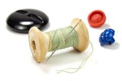 Bobina di legno d'annata del filo, dell'ago e dei bottoni verdi su fondo bianco Immagini Stock Libere da Diritti