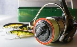 bobina di pesca ed esca di pesca sui precedenti della scatola con i richiami Fotografia Stock Libera da Diritti
