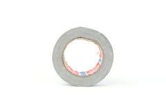 Bobina di riparazione dell'argento del rotolo del nastro di condotta su bianco Fotografie Stock Libere da Diritti
