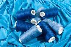 Bobinas azules de cuerdas de rosca en el paño azul Imagenes de archivo