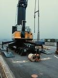 Bobinas de acero cargadas de la orilla al buque de carga Trabajador a las bobinas del slig para cargar por la grúa de la orilla i imágenes de archivo libres de regalías
