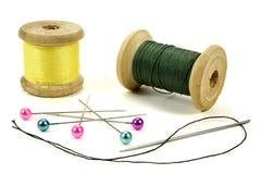 Bobinas de madera con los hilos, los pernos y la aguja para coser en un fondo blanco Fotos de archivo