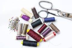 Bobinas del hilo, de los pernos y de las tijeras, artículos de costura para el sastre Craft en el fondo blanco Imagenes de archivo