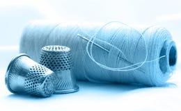 Bobinas del hilo y dedales de costura Foto de archivo libre de regalías