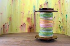 Bobine avec le fil tourné par main colorée Photos libres de droits