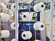 Bobine con il filo bianco alla fabbrica dell'indumento fotografia stock libera da diritti