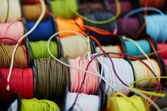 Bobine con la corda dei colori differenti per il cucito o l'elaborazione su un mercato immagine stock libera da diritti