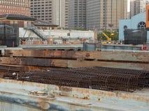 Bobine d'acciaio del tondo per cemento armato tra altra attrezzatura di spedizione in un bacino industriale nell'area urbana fotografie stock