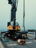 Bobine d'acciaio di carico dalla riva alla nave da carico Lavoratore alle bobine dello slig per il carico dalla gru della riva immagini stock libere da diritti