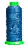 Bobine de couture avec le fil bleu et l'aiguille ci-jointe Image libre de droits