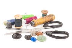 Bobine de fil avec des boutons et des ciseaux Images stock
