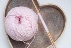 Bobine de fil de coton avec des aiguilles pour tricoter au-dessus de la boîte en bois de coeur pour le passe-temps et fait main r Photos libres de droits