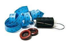 Bobine de fil, de boutons et de mètre noirs Images stock