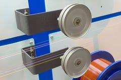 Bobine de fil en métal avec la fibre optique dans l'isolation colorée Photographie stock