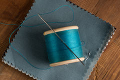 Bobine de fil et d'aiguille bleus sur des échantillons de tissu Photographie stock