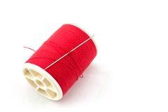 Bobine de fil et d'aiguille rouges Photographie stock