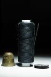 Bobine de fil noir avec un dé d'aiguille Image stock