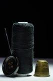 Bobine de fil noir avec une aiguille, dé, bouton Images stock