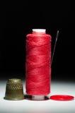 Bobine de fil rouge avec un dé d'aiguille Photos libres de droits