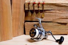 Bobine de pêche avec des amorces en métal sur le fond en bois Photos stock