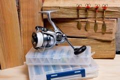 Bobine de pêche avec des amorces en métal sur le fond en bois Image stock