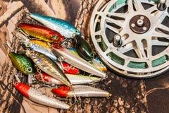 Bobine de pêche avec les wobblers fabriqués à la main pour pêcher sur le camouflage Image stock