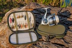 Bobine de pêche et divers genre d'amorces en métal sur le dos naturel Images stock