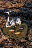 Bobine de pêche et divers genre d'amorces en plastique sur le Ba naturel Photo stock