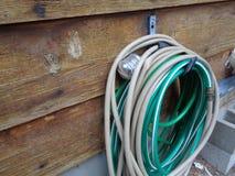 Bobine de tuyau contre Cedar Siding Wall image stock