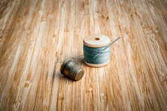 Bobine de vintage de fil avec le plan rapproché d'aiguille et de dé sur le vieux fond en bois image libre de droits