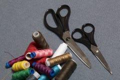 Bobine dei fili dei colori differenti su un fondo tessuto grigio Due paii di forbici delle dimensioni differenti Fotografia Stock Libera da Diritti