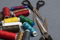 Bobine dei fili dei colori differenti su un fondo tessuto grigio Due paii di forbici delle dimensioni differenti Fotografie Stock Libere da Diritti
