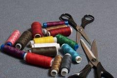 Bobine dei fili dei colori differenti su un fondo tessuto grigio Due paii di forbici delle dimensioni differenti Immagini Stock