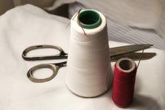 Bobine del filato cucirino con gli aghi e le forbici Fotografia Stock