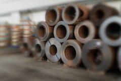 Bobine dell'acciaio impilate in un magazzino Fotografia Stock