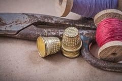Bobine delle forbici dei ditali dei filati cucirini su fondo d'annata Fotografie Stock Libere da Diritti