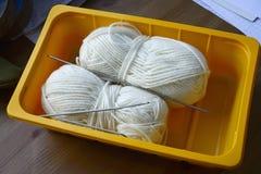 Bobine di lana e dei ferri da maglia bianchi in un raggiro della plastica di giallo Fotografie Stock Libere da Diritti