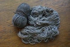 Bobine di lana grigia su una superficie di legno Immagini Stock Libere da Diritti