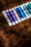 Bobine du fil de diverses couleurs sur le bureau en bois Photo stock